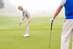 Lady golfer teeing off for the day watched by partner Royalty Free Stock Photography