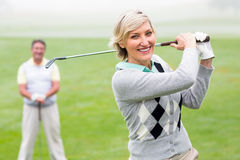 Lady golfer teeing off for the day watched by partner Stock Photography