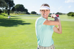 Lady golfer teeing off and smiling at camera Stock Photo