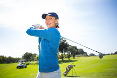Lady golfer teeing off and smiling Stock Images