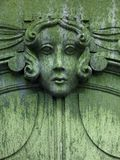 Lady in green. Ancient face of young lady, weathered sculpture Stock Photography