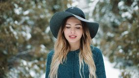Lady in green coat and hat walks around in the winter forest. Close up Portrait of stylish young beautiful woman in a stock footage