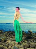 Lady in green dress on seashore Stock Image