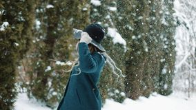 Lady in green hat and coat whirls under the falling snow in the forest.  stock footage
