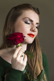 Lady in green with red rose. A young brown haired woman in a green sweater wearing red lipstick holding a red rose Royalty Free Stock Photo