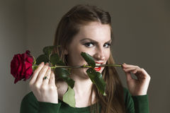 Lady in green with red rose. A young brown haired woman in a green sweater wearing red lipstick holding a red rose between her teeth Royalty Free Stock Images