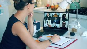 A lady is greeting her colleagues during a video conference call. Meeting online, remote work using videocall.