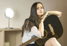 Lady and guitar. Beautiful young lady in a room with guitar Stock Photos