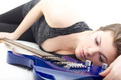 Lady with a guitar. Lovely brunette with an electric guitar over white royalty free stock images