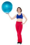 Lady gym instructor holding pilates ball Royalty Free Stock Images