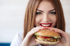 Lady with a hamburger for a table in a cafe