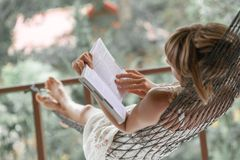Lady in a hammock. Woman in summer dress lies in the hammock in a garden and reads the book stock photo