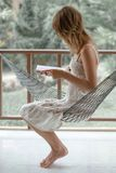 Lady in a hammock. Woman in summer dress sits in the hammock in a garden and reads the book stock photography