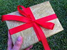 A lady hand is holding a gift box . A group of wrapped gift boxes for someone special in greeting moments. They're decorating with red satin ribbon. For stock photos