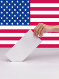 Lady hand putting a voting ballot in slot of white box of USA. Lady hand putting a voting ballot in slot of white box isolate and flag of USA Royalty Free Stock Photography