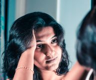 A lady handling and styling her hair by looking at mirror image.  royalty free stock images