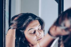 A lady handling and styling her hair by looking at mirror image.  royalty free stock photo