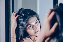 A lady handling and styling her hair by looking at mirror image.  royalty free stock photos