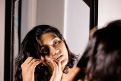 A lady handling and styling her hair by looking at mirror image.  royalty free stock photography
