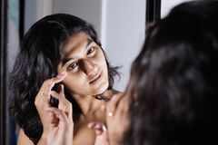 A lady handling and styling her hair by looking at mirror image.  stock image