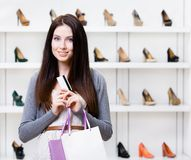 Lady hands credit card in footwear shop. Lady holds credit card in footwear shop with great variety of stylish shoes Stock Image