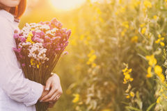 Lady, hands holding a bouquet of statice flowers, soft, spring sunset Stock Image