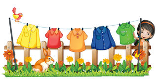 A lady hanging her clothes in the garden with a bird and a bunny Stock Photo