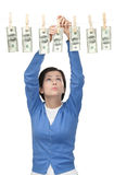 Lady hangs money on the line Royalty Free Stock Image