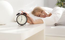 Lady has woken up by an alarm clock. eyes open Stock Photography