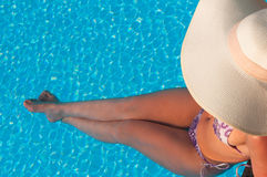 Lady in hat laying in the blue water Stock Photo