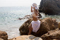 Lady in Hat and white lace dress on rocky beach Stock Photography