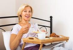 Lady having breakfast in bedroom Stock Image