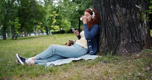Lady in headphones enjoying music using smartphone drinking coffee in park. Lady in wireless headphones is enjoying music using smartphone and drinking take out stock video