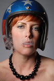Lady with helmet blowing smoke Stock Image