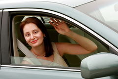 Lady in her car waving to someone. Smiling lady in her car waving to someone Stock Photography