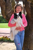 Happy Lady with Her Papillon Dog. Pretty lady posing with a black and white papillon dog leaning an a huge trunk of tree on a sunny day Royalty Free Stock Photo