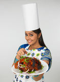 Lady with her roasted chicken. A traditionally dressed asian lady chef with her roasted chicken stock photo