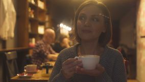 Lady in her 40s spending evening in cafe and drinking soft flavored cappuccino. Stock footage stock footage
