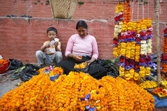 Lady and her son selling marigold necklaces Stock Image