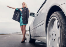 Lady in high heel shoes with broked car on the road Stock Image