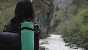 Lady hiker with backpack looking on hills and mountain river lake, girl enjoying nature panoramic landscape in trip. Relax holiday. Traveler woman exploring stock footage
