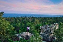 Lady hiker with backpack standing on top of the mountain and enjoying valley view at sunset.  royalty free stock image