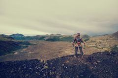 Lady hiker with backpack standing on top of the mountain, view from volcano peak to frozen lava valley.  stock image