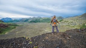 Lady hiker with backpack standing on top of the mountain, view from volcano peak to frozen lava valley.  royalty free stock photography