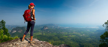 Lady hiker on the mountain. Lady hiker with backpack standing on top of the mountain and enjoying valley view Royalty Free Stock Photos