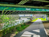 Lady hiker sitting under railway a bridge. Beside the River Lea in East London royalty free stock photos