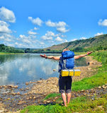 Lady hiker standing on the grass and enjoying view of the river Stock Photos