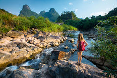 Lady hiker standing on the rock. And enjoying view of the river royalty free stock photography