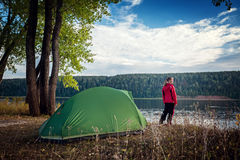 Lady hiker. Lady standing by the tent near river coast stock photo