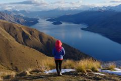 Lady hiker standing on top of the mountain - isthmus peak with a view of the Wanaka Lake. In the afternoon stock photography